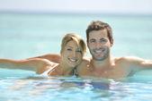 Couple swimming in infinity pool — Stock Photo