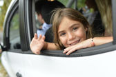 Girl waving hand by car window — Stockfoto