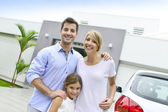 Parents with kid standing in front of home — Stock Photo