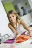 Girl helping putting the table — Stock Photo