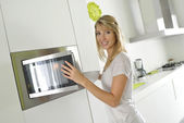 Woman using microwave oven — Stock Photo