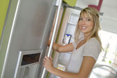 Young woman opening fridge — Stock Photo