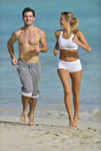 Couple jogging on a sandy beach — Stock Photo