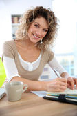 Saleswoman writing on agenda — Stock Photo