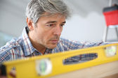 Craftsman using level — Stockfoto