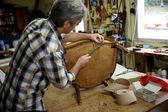 Craftsman repairing armchair — Stock Photo