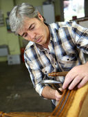 Craftsman repairing armchair — Stock fotografie