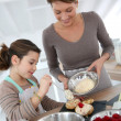 Stock Photo: Mother and daughter preparing puffs