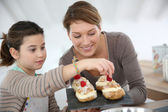 Mother and daughter preparing puffs — Stock Photo