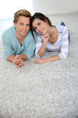 Couple laying on carpet floor — Stock Photo