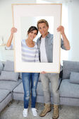 Couple holding picture frame — Stock Photo