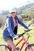 Usmívající se dívka jedoucí na kole — Stock fotografie