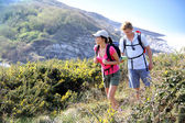 Couple of hikers on country field — Stockfoto