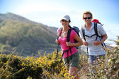 Couple of hikers on country field — Stock Photo