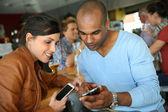 People in coffee shop using smartphones — Stock Photo