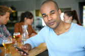 Man in bar checking messages — Stock Photo