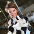 Woman carrying baby goat — Stock Photo