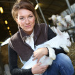 Woman carrying goat in barn — Stock Photo