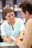 Pharmacist showing pills to customer — Stock Photo