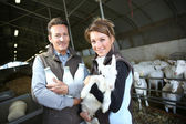 Couple holding goat and milk — Stock Photo