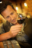Winegrower holding glass of wine — Stock Photo