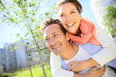 Man giving piggyback ride in park — Stock Photo