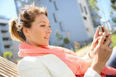 Woman in park using smartphone — Stock Photo