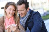 Mature couple with smartphone — Stockfoto