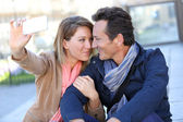 Embracing couple taking picture — Stock Photo