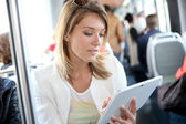 Woman in city train websurfing — Stock Photo