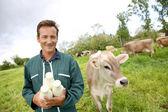 Farmer holding bottles of milk — Stock Photo