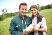 Couple holding bottles of milk — Stock Photo