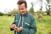 Farmer in field using smartphone — Stock Photo
