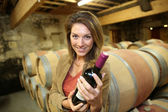 Woman holding bottle of wine — Stock Photo