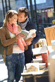 Couple walking by book fair — Stock Photo