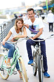 Couple on bikes on promenade — Stock Photo