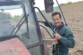 Agricultor subindo no trator para fora — Fotografia Stock