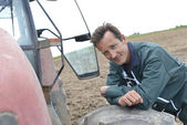 Farmer leaning on tractor — Stockfoto