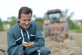 Farmer checking on ground — Stock Photo