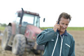 Farmer with phone in field — Stock Photo