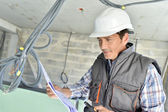 Worker checking blueprint on site — Stock Photo