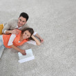 Couple on carpet using tablet — Stock Photo #47819621