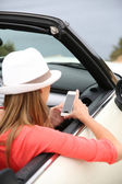 Girl using smartphone in car — Stock Photo