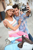 Couple taking picture on scooter — Foto Stock