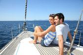 Couple navigating on sailboat — ストック写真