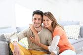 Embracing couple on sofa — Stock Photo