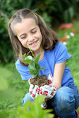 Girl holding plant — Stock Photo