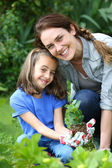 Girl with mother in garden — Stock Photo