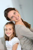 Mother and daughter sitting back to back — Stock Photo