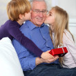 Kids giving birthday gift to their grandfather — Stock Photo #6698592